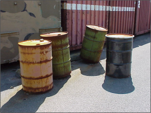 Rusted, bulging 55-gal drums.